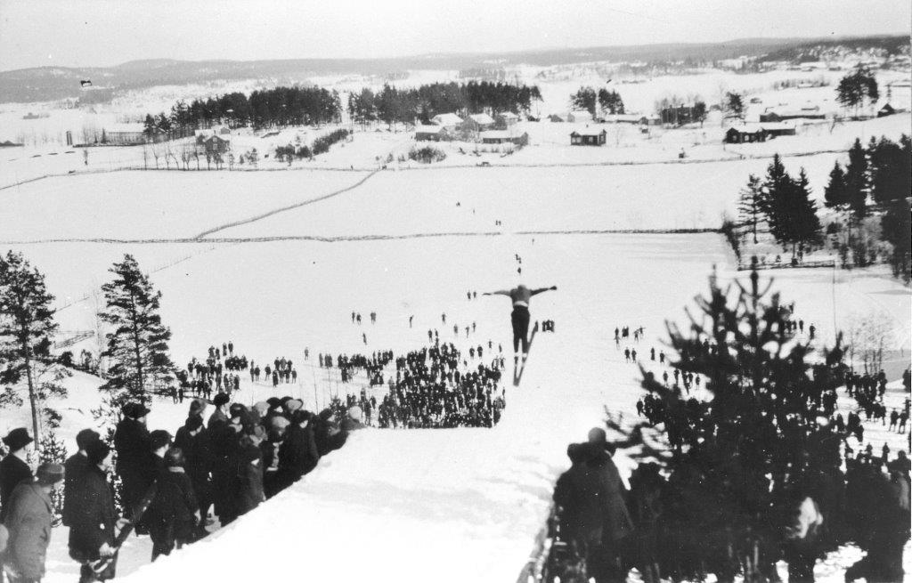 Paanamäen hyppyrimäki Oinolan kylässä, taustalla (kaukana) koulu